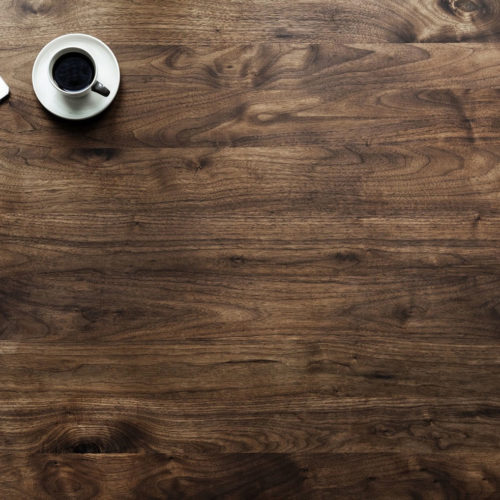 En bordsskiva med en surfplatta och en kopp kaffe.