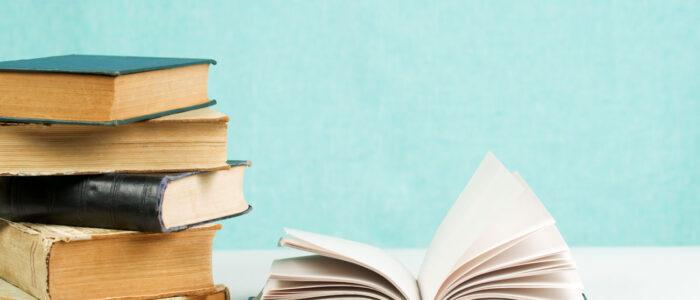 En stapel med böcker, med en uppslagen bok.