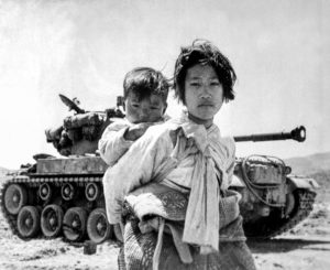 Med sin lillebror på ryggen passerar en koreansk flicka på flykt framför en M-26 Pershingstridsvagn, Haengju 1951